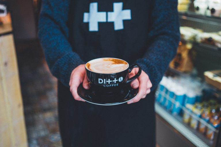 Someone holding coffee at Ditto Coffee Manchester