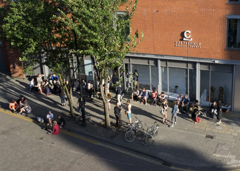 An audeince gathers outside Castlefield Gallery on a sunny day