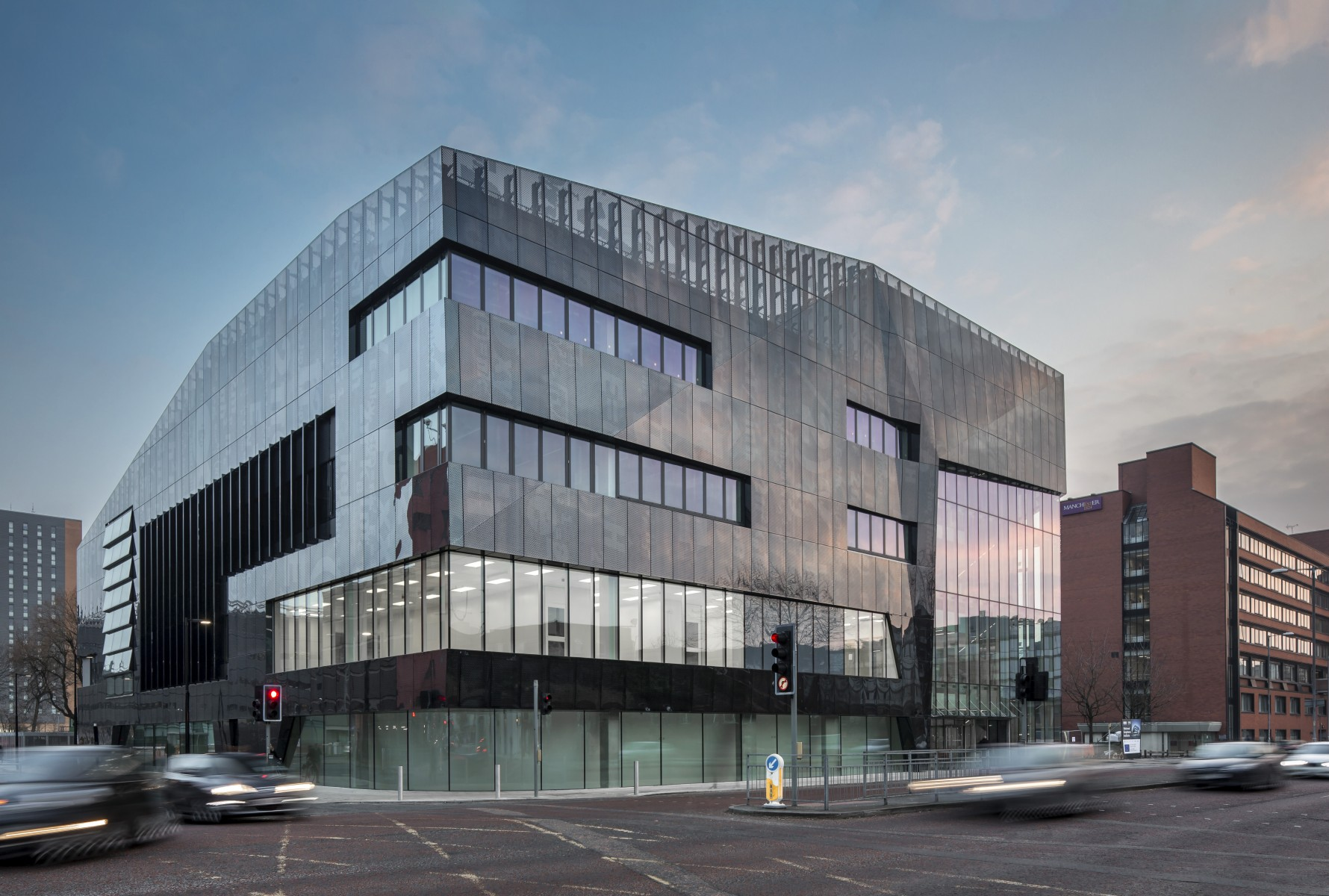 External shot of National Graphene Institute with sun reflecting on glass windows