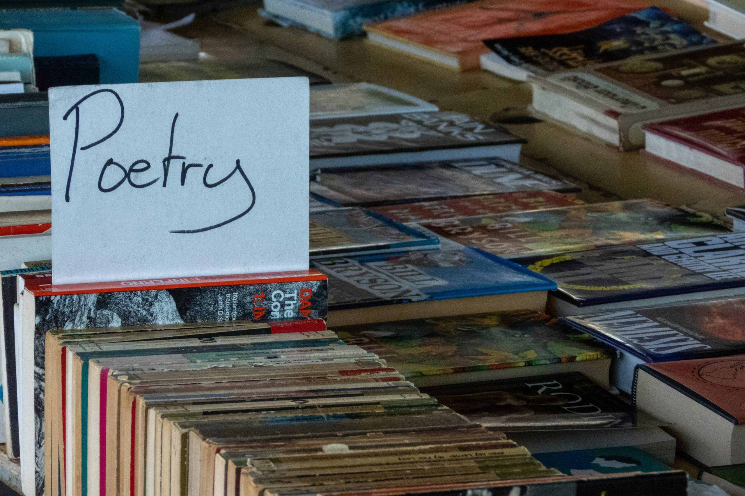 """Image of a sign reading """"poetry"""" on a pile of books"""