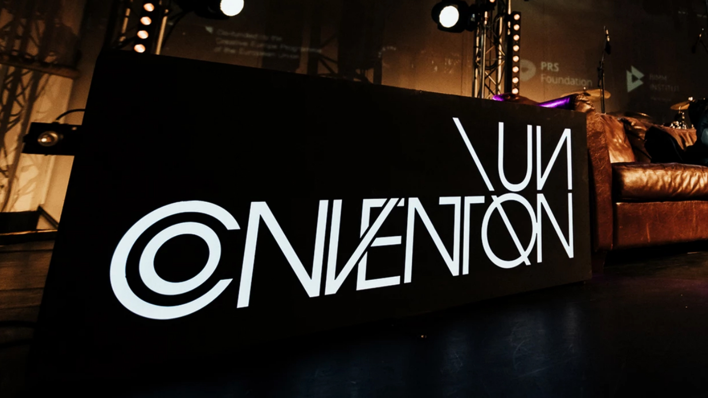 A lit sign with the Un-Convention logo on a stage