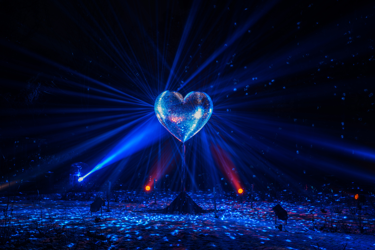 Light reflects off the heart-shaped mirror ball for Our Beating Heart