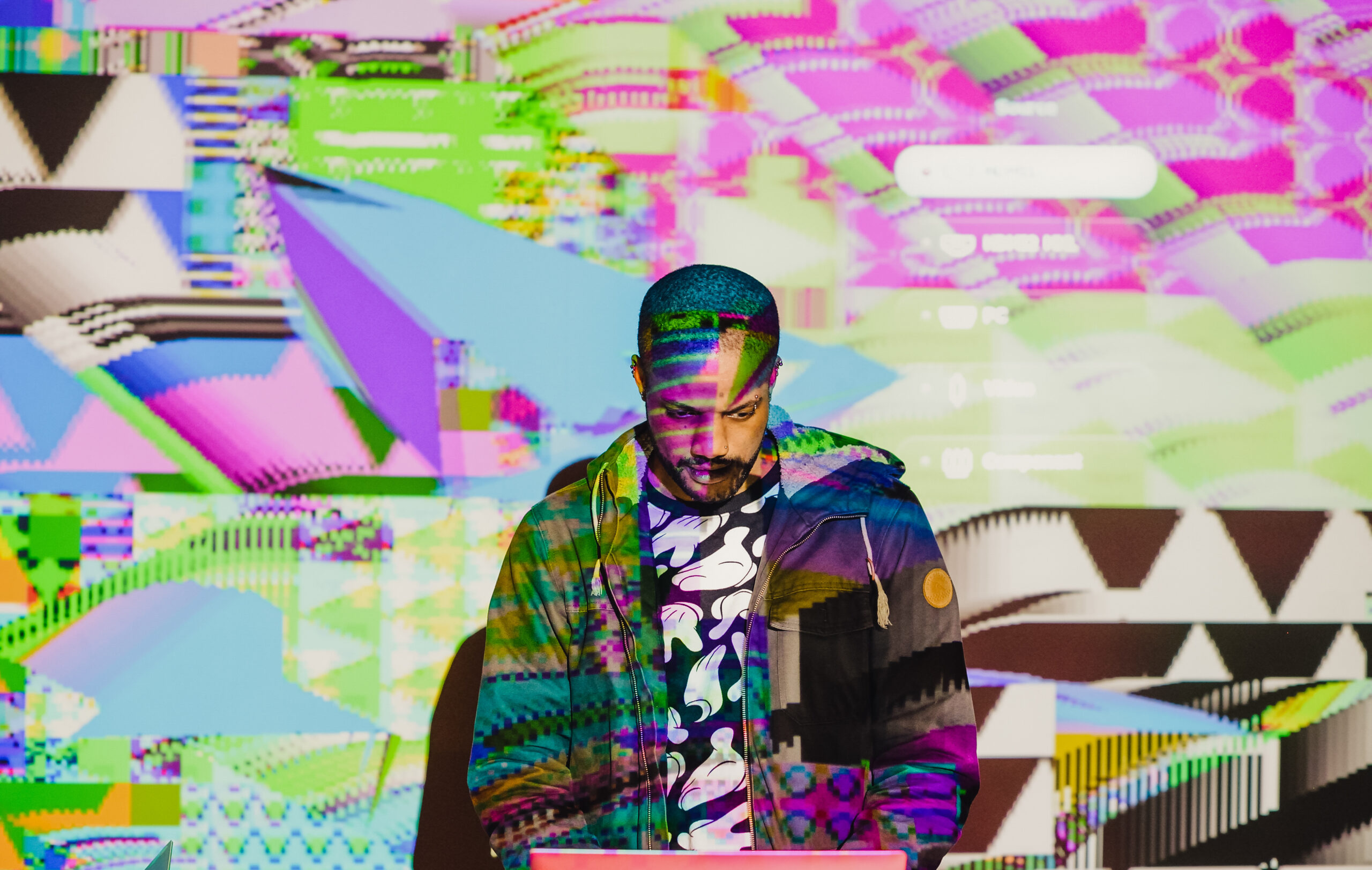 Artist Antonio Roberts, creator of Move Fast and Brake Things, looking at a laptop with projections across his body